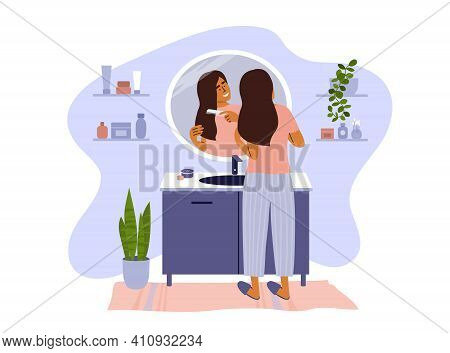 Scene Of Daily Morning Or Evening Routine. Female Standing In Bathroom Combing Hair Looking At Refle
