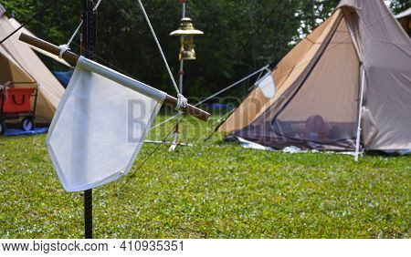 Focus At White Pennant Hanging On Black Metal Pole With Blurred Background Of Field Tents In Campsit