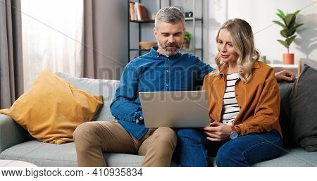 Caucasian Middle-aged Happy Married Couple Bearded Man And Beautiful Woman Sitting On Couch In Good
