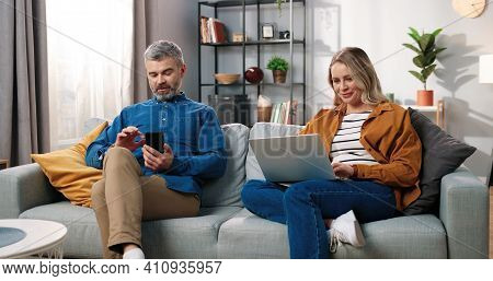 Happy Married Couple Resting At Home On Sofa In Living Room Using Digital Gadgets. Middle-aged Cauca