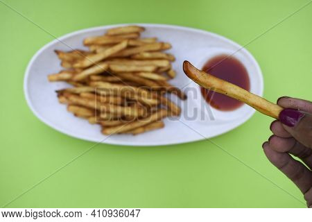 Female Holding A Plate Of Crispy Crunchy French Fries Heap. Potato Finger Chips With Seasoning Masal