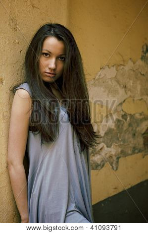 Young Beautiful Female Model Standing Near The Old Yellow Wall