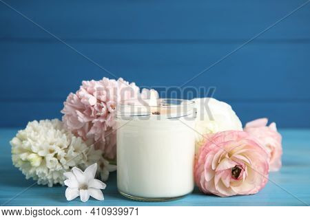Scented Candle With Burning Wooden Wick And Flowers On Blue Table