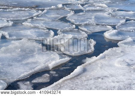 Spring Background With Melting Ice On The Surface Of A Frozen Bay. Snowy Shore Of A Frozen Lake.