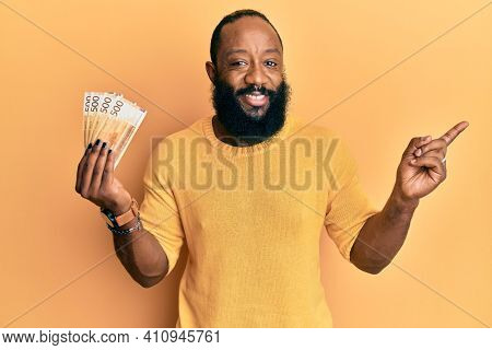 Young african american man holding 500 norwegian krone banknotes smiling happy pointing with hand and finger to the side