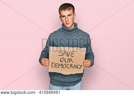 Young blond man holding save our democracy protest banner thinking attitude and sober expression looking self confident