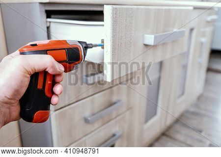 Assembling Elements Of Kitchen Furniture In A Vintage Style, The Master Turns The Screw With An Elec