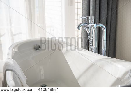 Old Style Bath Tub In Elegant Luxury Resort Bathroom. Sunny Window View Over. White Interior Bathtub