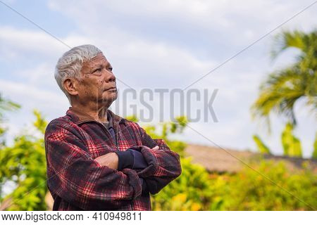Portrait Of An Elderly Asian Man With Gray Hair, Arms Crossed And Looking Up While Standing In A Gar