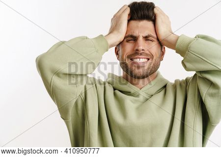 Displeased handsome man in sportswear posing and holding his head isolated over white background