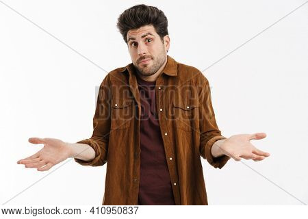 Perplexed young unshaven man showing and holding copyspace isolated over white background