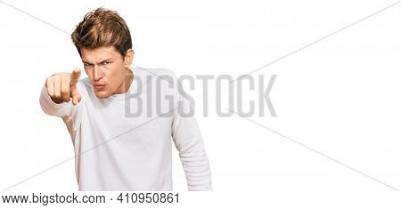 Handsome caucasian man wearing casual white sweater pointing displeased and frustrated to the camera, angry and furious with you