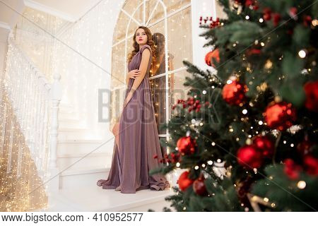Beautiful Girl Happy And Smiling In Evening Dress With Make-up And Hairdo Decorates Christmas Tree R