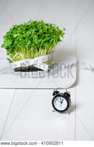 Micro-green On The Scale For Measuring Body Weight, Centimeter Tape For The Body, Clock On A Light B
