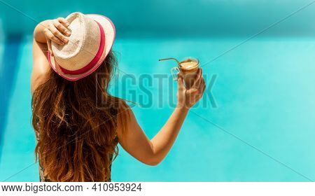 Young Slender Girl In Hat Sits By The Pool In The Summer At The Hotel And Drinks Cold Coffee. Woman