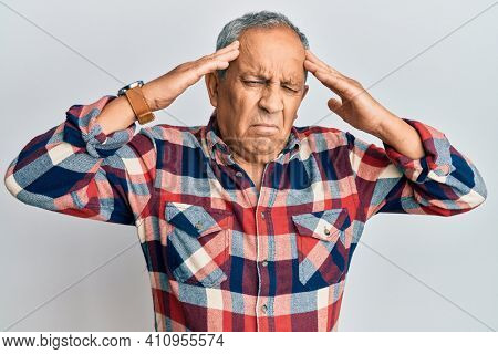 Senior hispanic man wearing casual clothes with hand on head, headache because stress. suffering migraine.