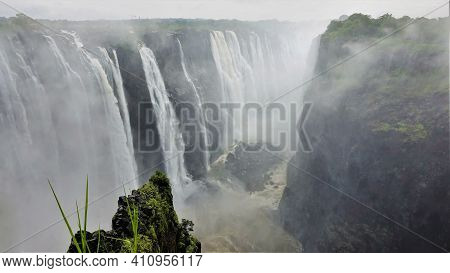The Streams Of Victoria Falls Plunge Into The Gorge. The Stormy Zambezi River Flows At The Bottom. A