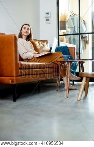 Woman Sitting On The Sofa At Home With Laptop