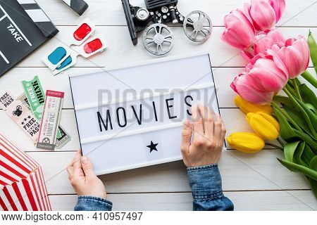 Top View Of Woman Hands Holding Lightbox With Word Movies, Clapper Board, Tickets And 3D Glasses