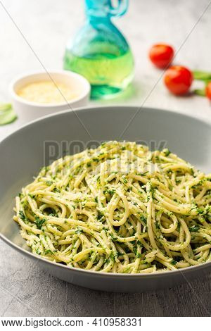 Spaghetti Pasta With Spinach Sauce And Parmesan Cheese On Concrete Background