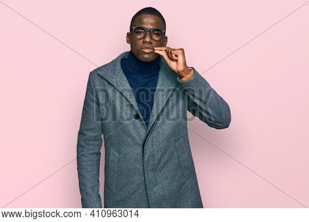 Young african american man wearing business clothes and glasses mouth and lips shut as zip with fingers. secret and silent, taboo talking