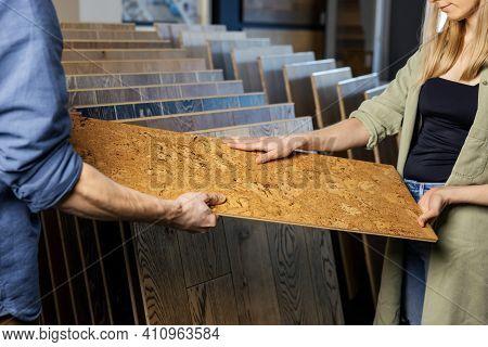 Young Couple Choosing Cork Floor For Home Improvements In Flooring Shop