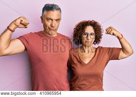 Beautiful middle age couple together wearing casual clothes strong person showing arm muscle, confident and proud of power