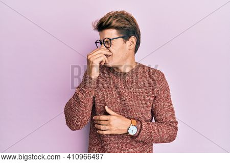 Handsome caucasian man wearing casual sweater and glasses smelling something stinky and disgusting, intolerable smell, holding breath with fingers on nose. bad smell