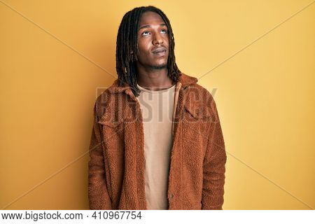 African american man with braids wearing brown retro jacket smiling looking to the side and staring away thinking.