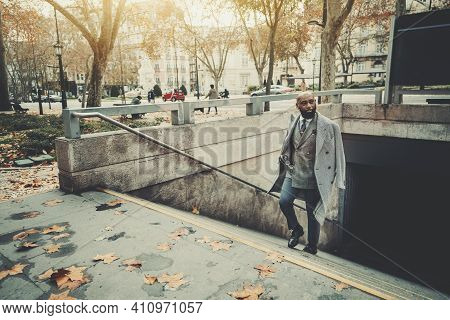 A Dapper Mature Bald Black Man Entrepreneur In A Fashionable Custom Plaid Costume And A Coat, With A