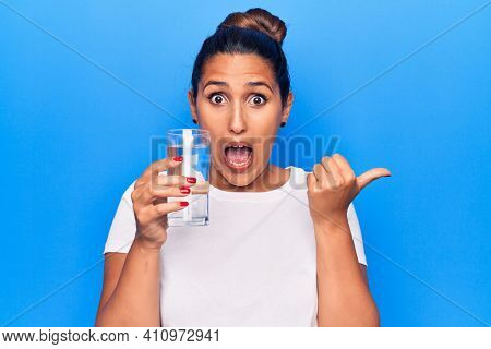 Young beautiful brunette woman drinking glass of water pointing thumb up to the side smiling happy with open mouth