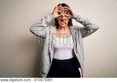 Young beautiful brunette sportswoman wearing sportswoman training over white background doing ok gesture like binoculars sticking tongue out, eyes looking through fingers. Crazy expression.