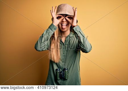 Beautiful blonde explorer woman with blue eyes wearing hat and glasses using binoculars doing ok gesture like binoculars sticking tongue out, eyes looking through fingers. Crazy expression.