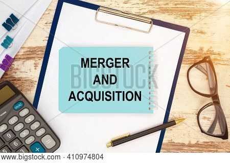 Notebook With Text - Merger And Acquisition, On The Office Table, Documents, Calculator, Glasses And