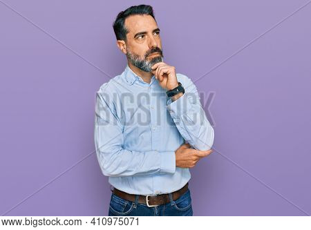 Middle aged man with beard wearing business shirt with hand on chin thinking about question, pensive expression. smiling with thoughtful face. doubt concept.