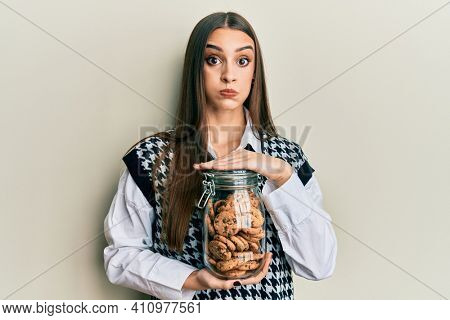 Beautiful brunette young woman holding jar of chocolate chips cookies puffing cheeks with funny face. mouth inflated with air, catching air.
