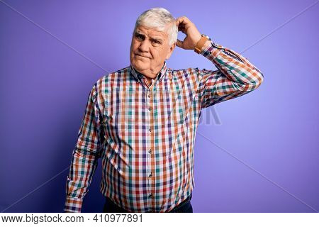 Senior handsome hoary man wearing casual colorful shirt over isolated purple background confuse and wondering about question. Uncertain with doubt, thinking with hand on head. Pensive concept.