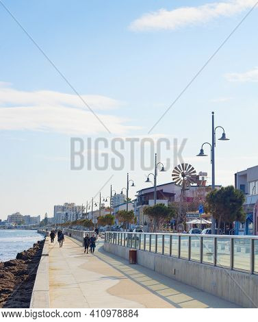 Larnaka, Cyprus - Feb 18, 2019: People Walking By Larnaca City Embankment With Typical Architecture