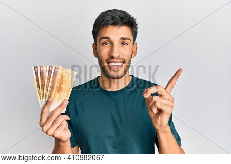 Young handsome man holding 500 norwegian krone banknotes smiling happy pointing with hand and finger to the side