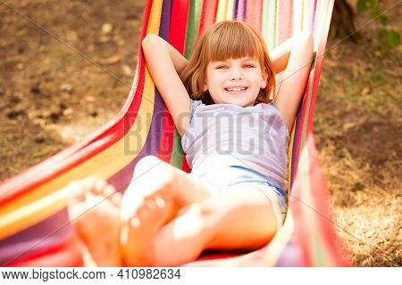Summer Vacation. Lovely Child Girl Rest In Colorful Hammock Outdoor In Summer Forest
