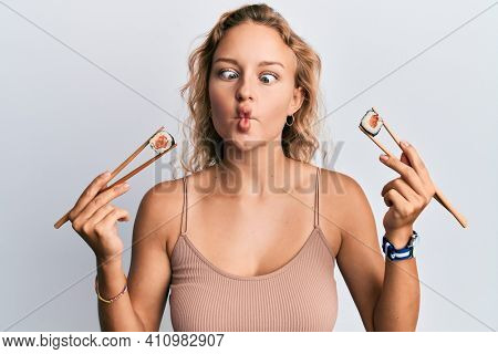 Beautiful caucasian woman eating sushi using chopsticks making fish face with mouth and squinting eyes, crazy and comical.
