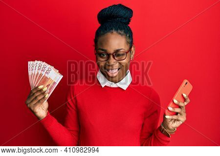 Young african american woman using smartphone holding norwegian krone banknotes winking looking at the camera with sexy expression, cheerful and happy face.