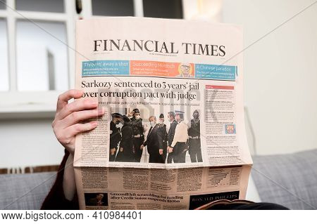 Paris, France - Mar 2, 2021: Curious Woman Reading Financial Times Newspaper With Headline Former Fr