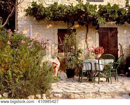 A Quaint, Pretty Garden Scene, With Rustic Patio Furniture And Ornamental Flowers Outside A Country