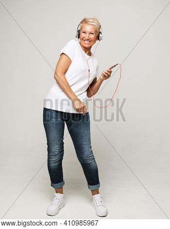 happy senior woman with short white hair wearing white tshirt listening to music with headphones
