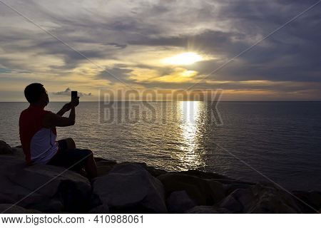 A Man Wearing Face Mask Uses A Smartphone To Take Pictures Of Beautiful Sunset In Tanjung Aru Kota K