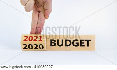 Business Concept Of Budget Planning 2021. Businessman Flips Wooden Cube And Change Words 'budget 202