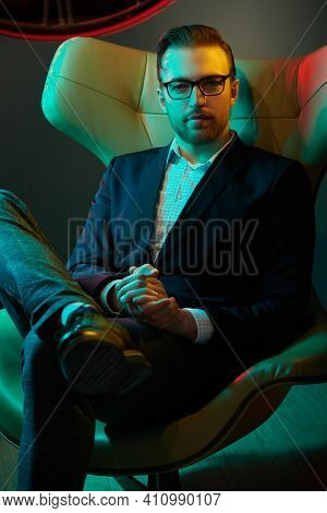 Portrait of a respectable middle-aged man in an elegant suit and glasses sitting in a leather armchair in a luxurious apartment. Men's fashion. Success and rich lifestyle. Businessman.