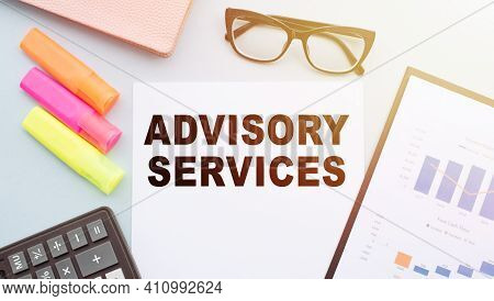 The Text Advisory Services On Office Desk With Calculator, Markers, Glasses And Financial Charts.