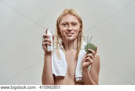 Cheerful Young Caucasian Man With Long Fair Hair Holding Facial Sponge And Cleaning Foam While Posin